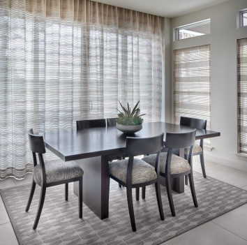 contemporary dining table with upholstered chairs and sheer window curtains and roman shades