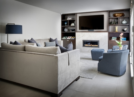 Family room with grey custom sofa and blue chairs in front of tv above contemporary fireplace