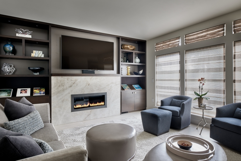 tv above contemporary fireplace with custom built-in cabinets in family room