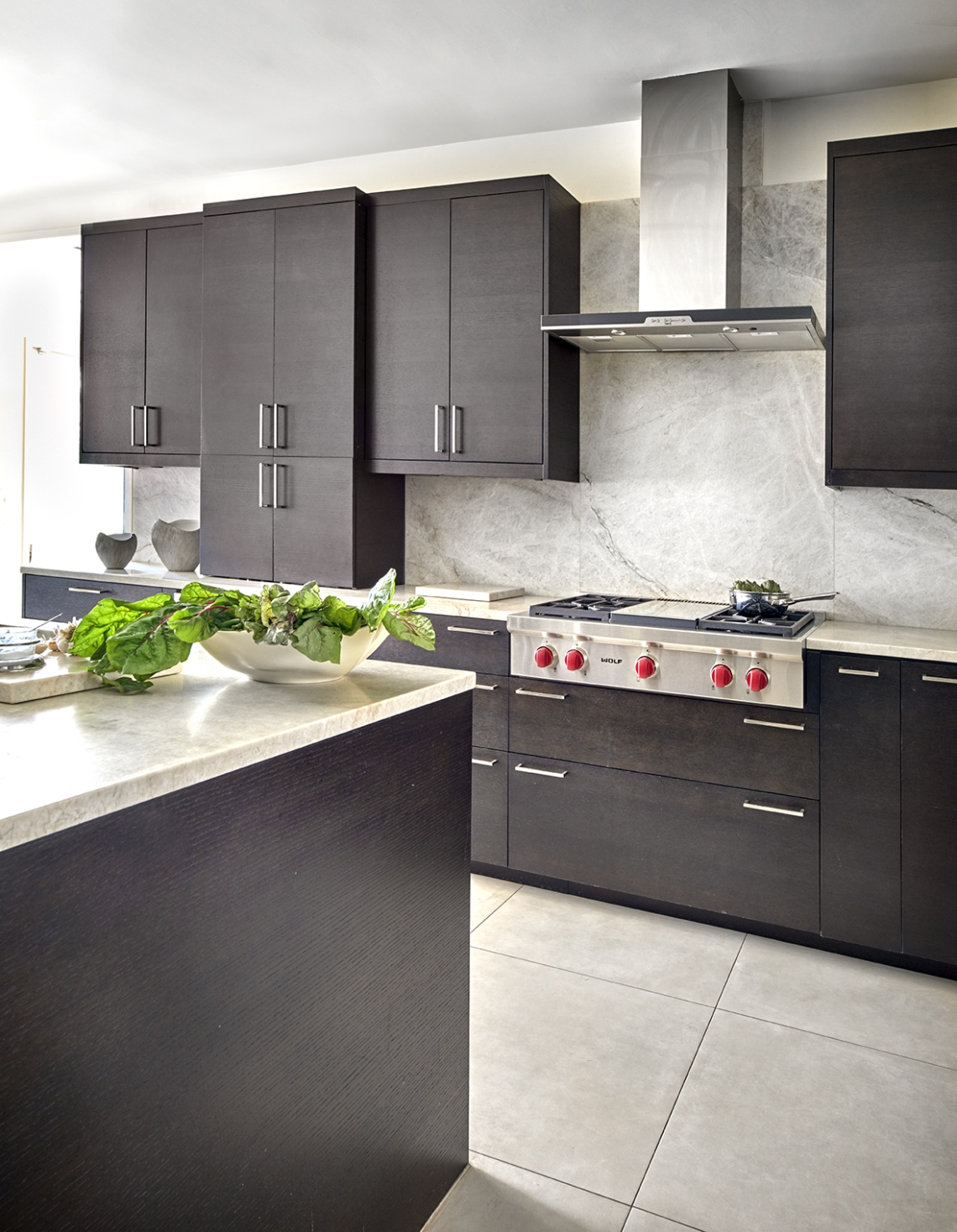 warm contemporary kitchen with dark oak cabinets and Wolf range top with full height quartzite backsplash and appliance garage