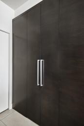 hidden pantry doors in contemporary kitchen with dark oak cabinets