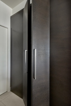 hidden pantry in contemporary kitchen with dark oak cabinetry