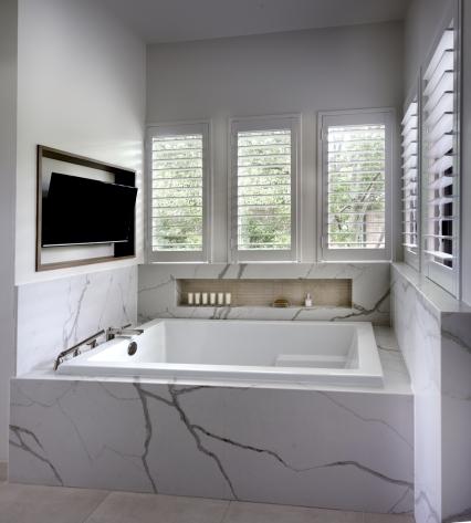 TV above drop-in bathtub with quartz surround and recessed niche under windows