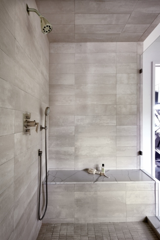 Custom shower with stacked porcelain tile and Daltile One quartz shower bench top