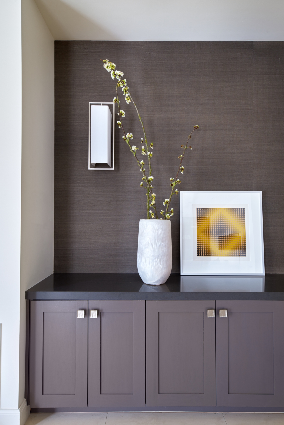 dark brown textured wallpaper with sconce above grey shaker cabinetry