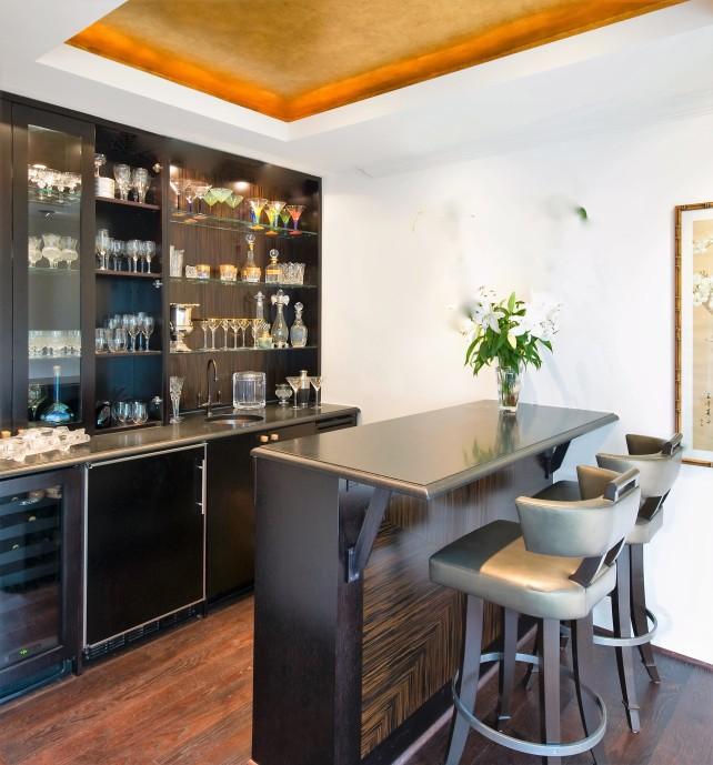 contemporary home bar with macassar ebony panel and grey bar stools