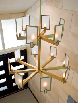 gold entry and foyer chandelier above limestone wall and contemporary front door
