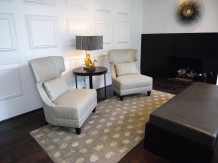 pair of neutral chairs on top of polka dot rug and in front of paneled wall