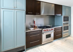 green kitchen with stainless steel countertops and backsplash and wolf range