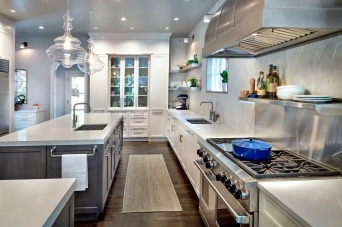 designer kitchen with white glass cabinetry and blown glass pendants