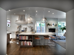 custom vent hood and kitchen island with open shelving and bar stools and pendants